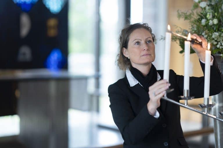 Kvinne tenner et lys i begravelse