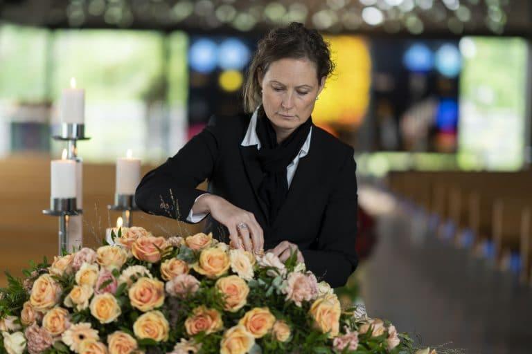 Kvinne ordner blomsterdekorasjon på kiste